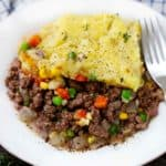 A close up photo of a white plate with shepherd's pie and a fork.