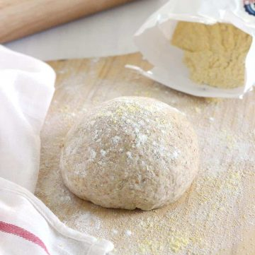 Whole wheat pizza dough on a cutting board.