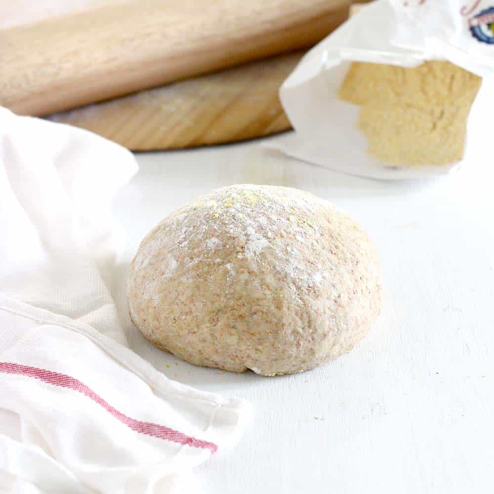 Ball of whole wheat pizza dough on a white surface.