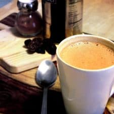 White mug with hot chocolate inside, on a wooden table with spoon and cutting board in the background.