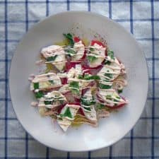Plate of tomato slices topped with mozzarella slices, basil, and creamy sauce.