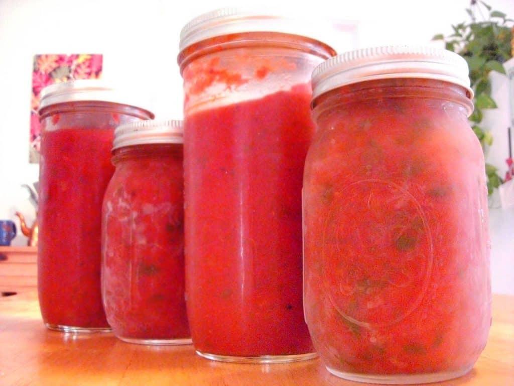 Four glass jars filled with marinara sauce.