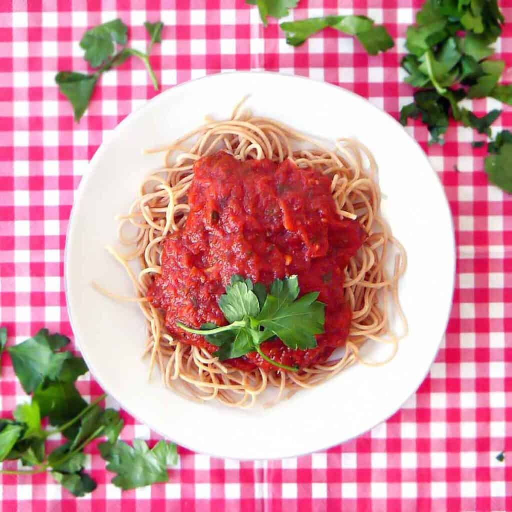 Top down view of pasta with marinara sauce white plate on red and white checkered tablecloth, sprinkled with torn basil.