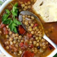 A close up photo of Greek Lentil Soup with buttered bread and a spoon in the bowl.