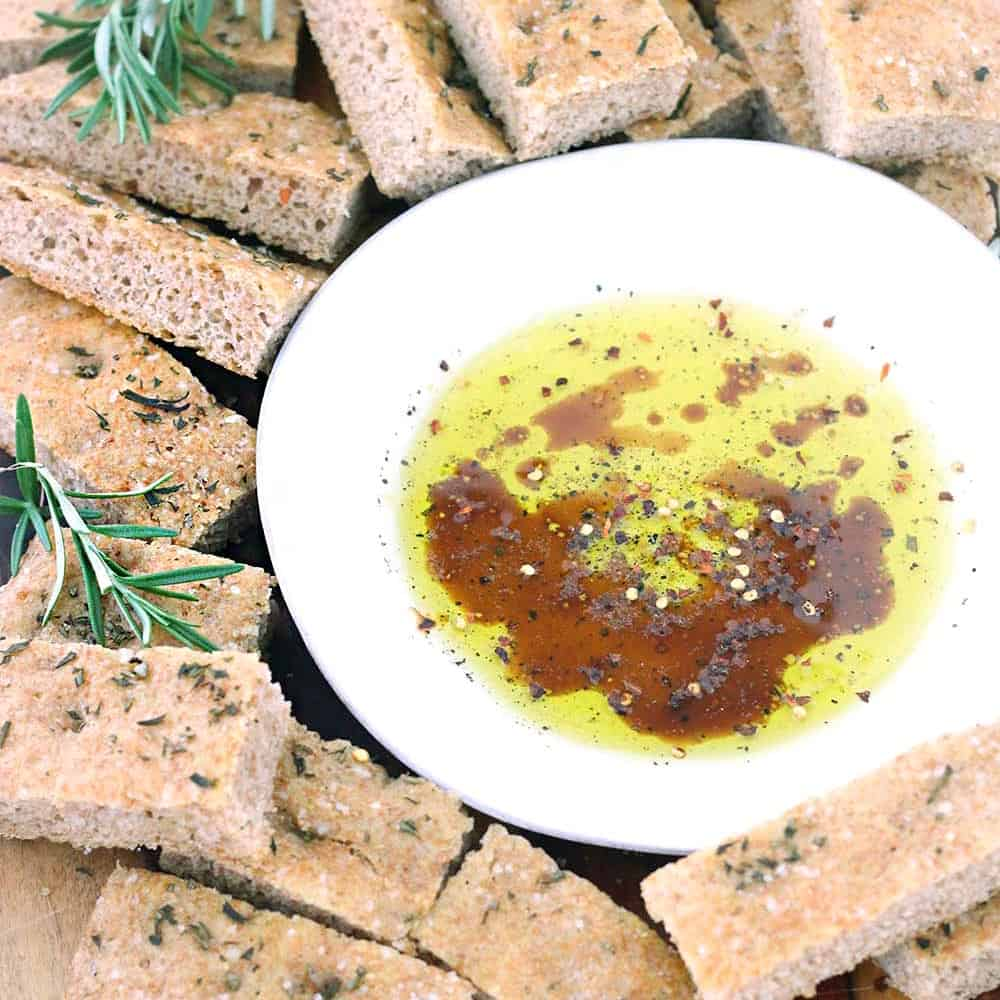 Olive oil, balsamic vinegar, and herbs in a shallow white bowl surrounded by pita chips.