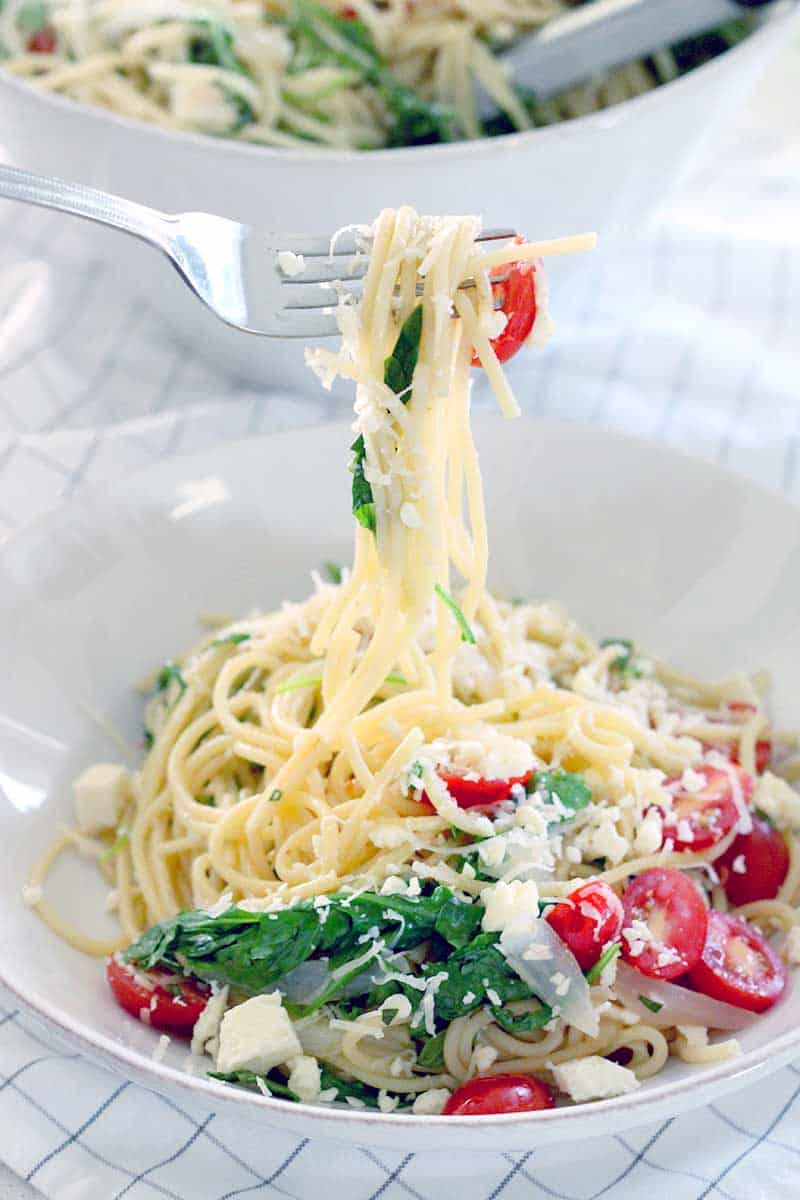 Fork twirling pasta with tomatoes, greens, and cheese, and lifted over a white plate.