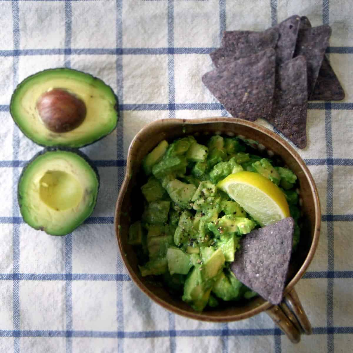 Bird's eye view of avocado salsa in brown ceramic bowl, surrounded by halved avocados and tortilla chips.