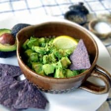 Avocado salsa in a brown ceramic bowl with handle, surrounded by tortilla chips and avocados.
