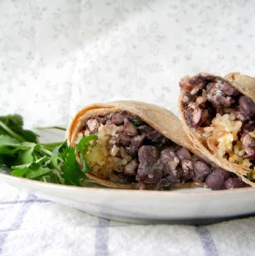 Close up of black bean and rice burritos on a white plate with herb garnish.