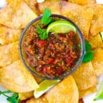 Bird's eye view of salsa in a white bowl on a blue and white striped tablecloth, surrounded by tortilla chips and lime slices.