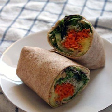 A veggie wrap cut in half, on a white plate.