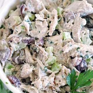 A bowl of chicken salad with grapes and walnuts.