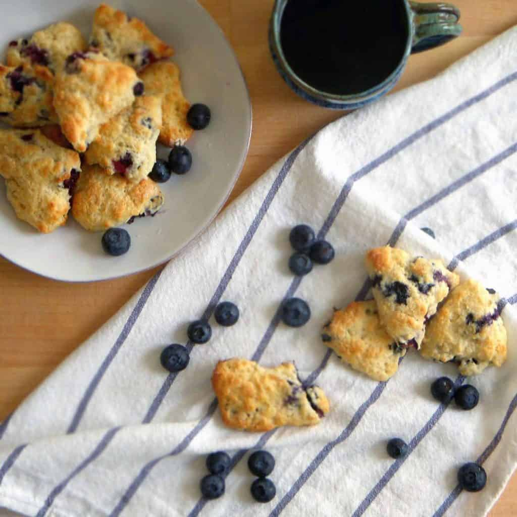 Bird's eye view of mini blueberry scones in a white plate and scattered to the side on a white towel, next to scattered fresh blueberries.