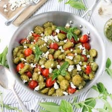 Pesto coated gnocchi with cherry tomatoes and goat cheese in a steel pan, viewed from above.