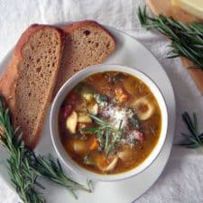 Bird's eye view of minestrone soup in a white bowl, on a white plate, with bread slices and a sprig of rosemary on the side.
