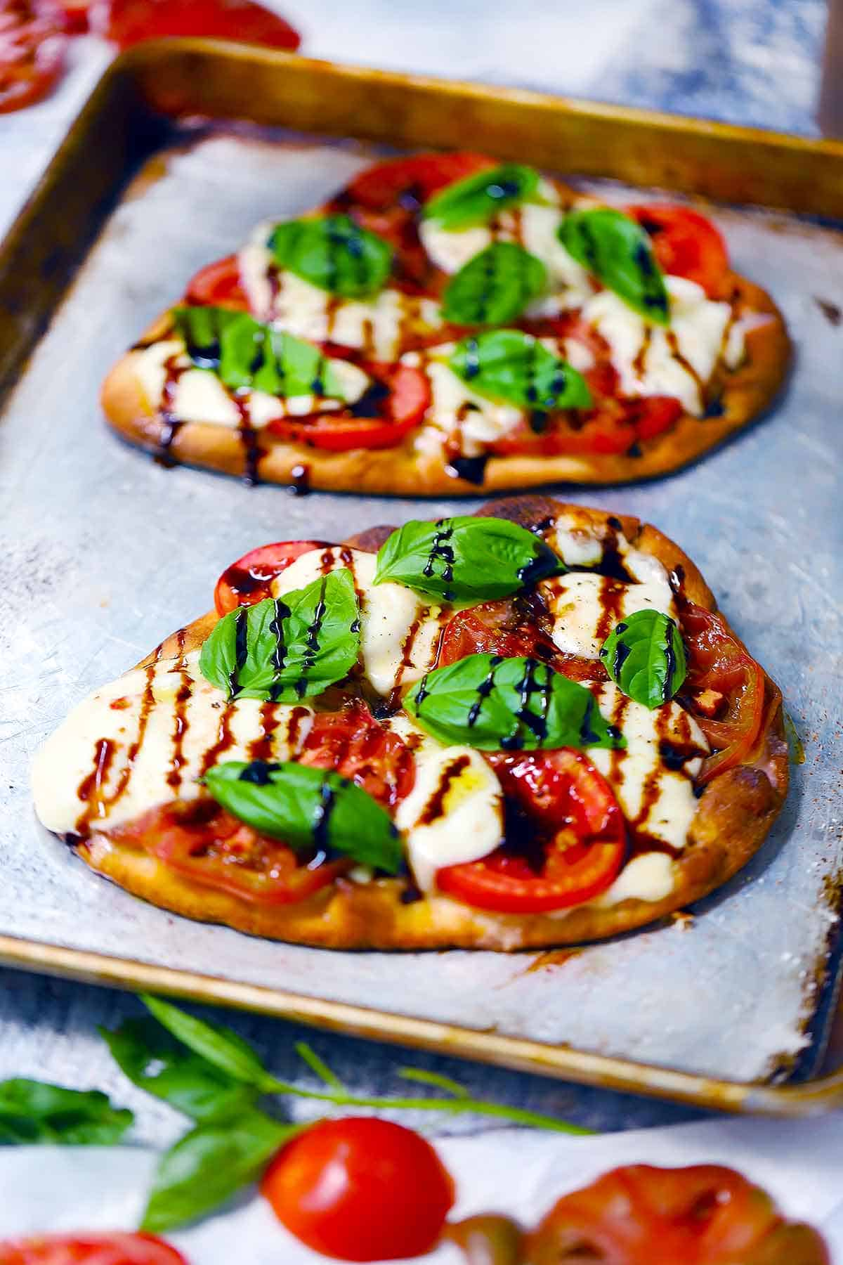 Pizza caprese includes fresh tomatoes, mozzarella, and basil on whole wheat pizza crust with an extra drizzle of olive oil and salt: delicious, fresh, and light.