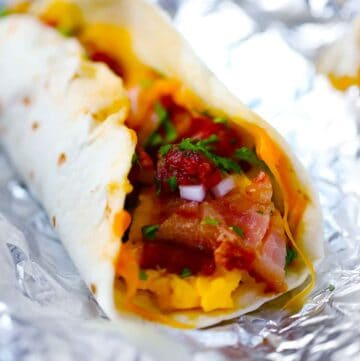 Tortilla with eggs, cheese, meat, and greens in the middle, placed on foil.