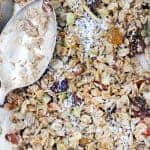 Close up bird's eye view of a layer of granola, with a silver antique spoon on the side.