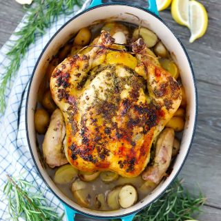 A whole chicken roasted in a blue cast iron enamel dutch oven with potatoes.
