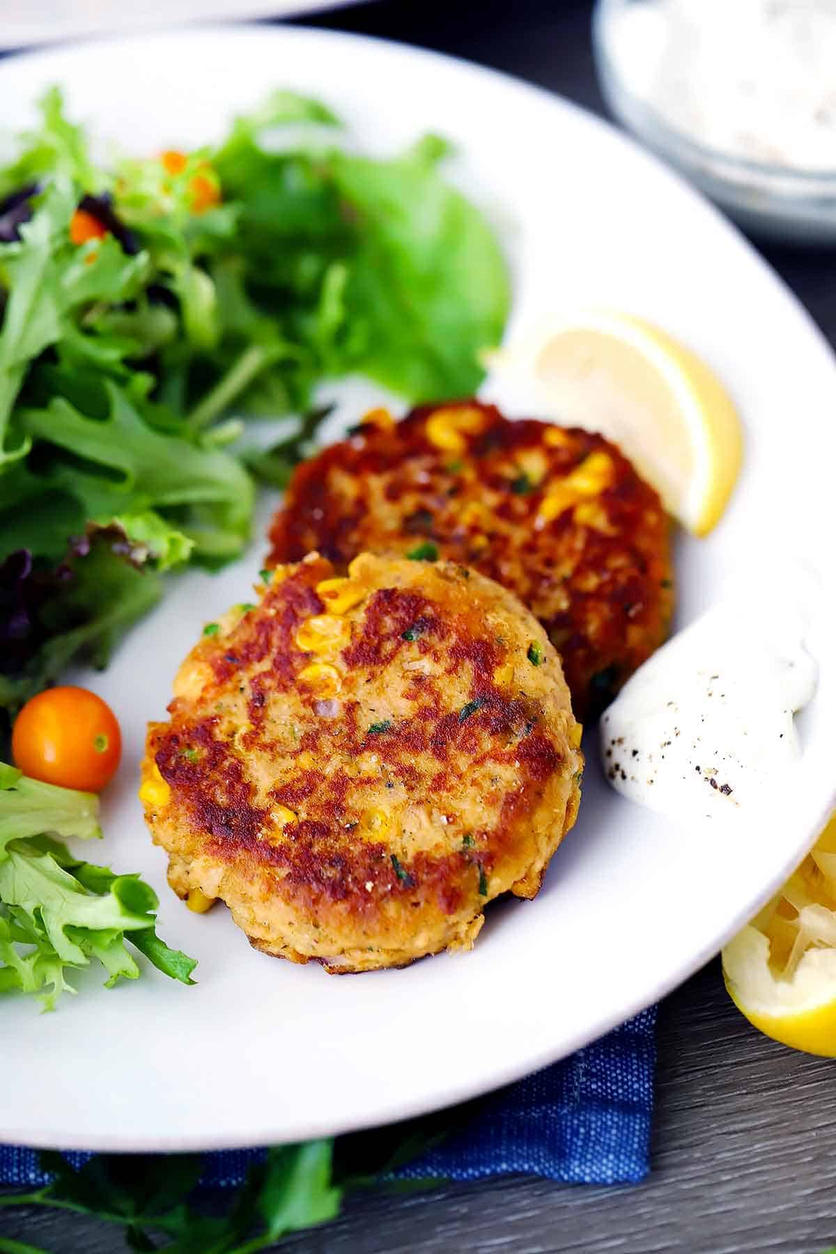Two salmon cakes on a white plate with a lemon wedge and a salad.
