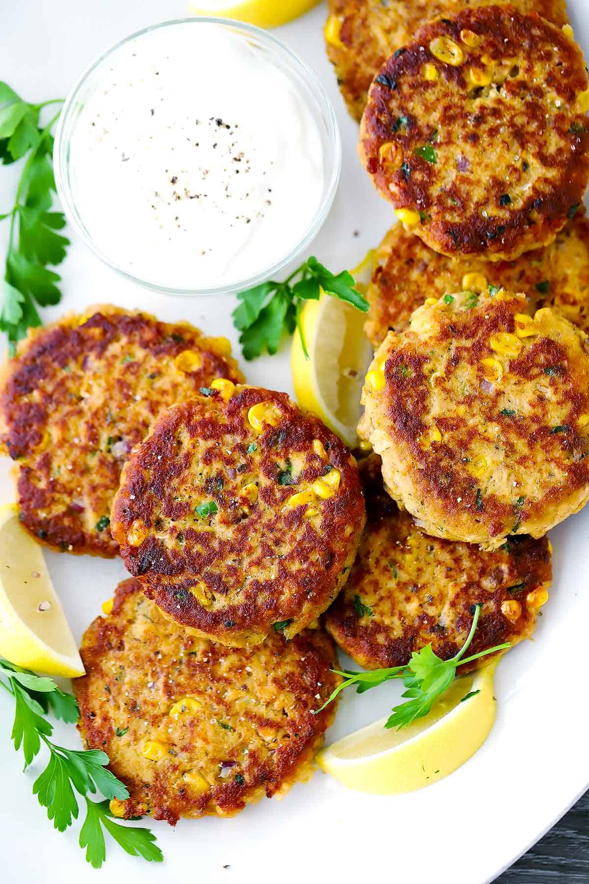 Salmon croquettes with creamy lemon sauce on a white platter.