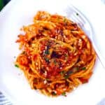 Close up of linguine coated in red sauce in a white shallow bowl.