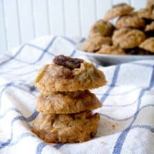 Three maple oatmeal raisin cookies stacked on a blue and white checkered cloth.