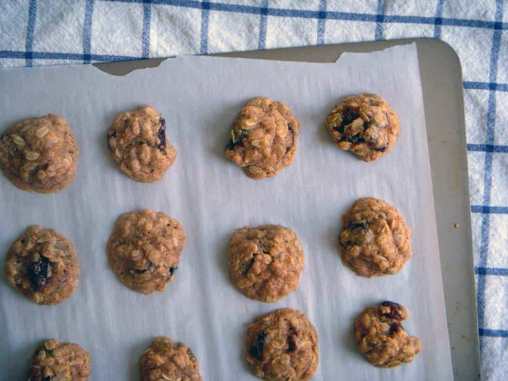 Maple oatmeal raisin cookies on parchment paper a baking sheet.