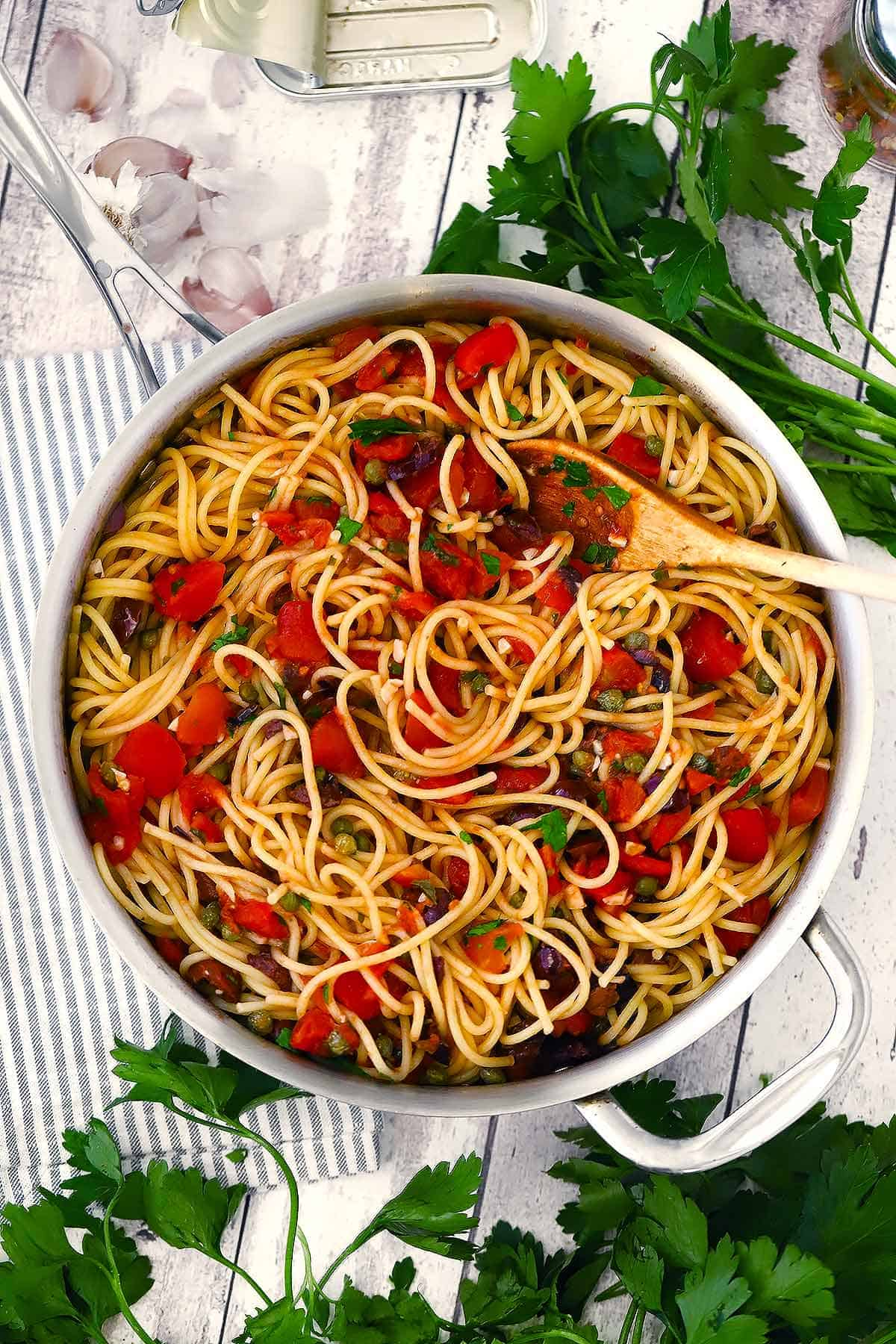 Overhead photo of a large skillet with spaghetti alla puttanesca in it and a wooden spoon.