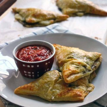 spinach and mushroom calzones (homemade hot pockets!) | A delicious homemade calzone, freezable for a quick lunch. Puff pastry is used for the crust, with spinach, mushrooms, and mozzarella for the filling, served with a side of marinara.