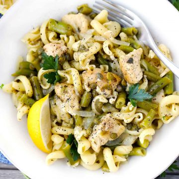 Chicken piccata pasta with green beans on a white plate with a lemon wedge.