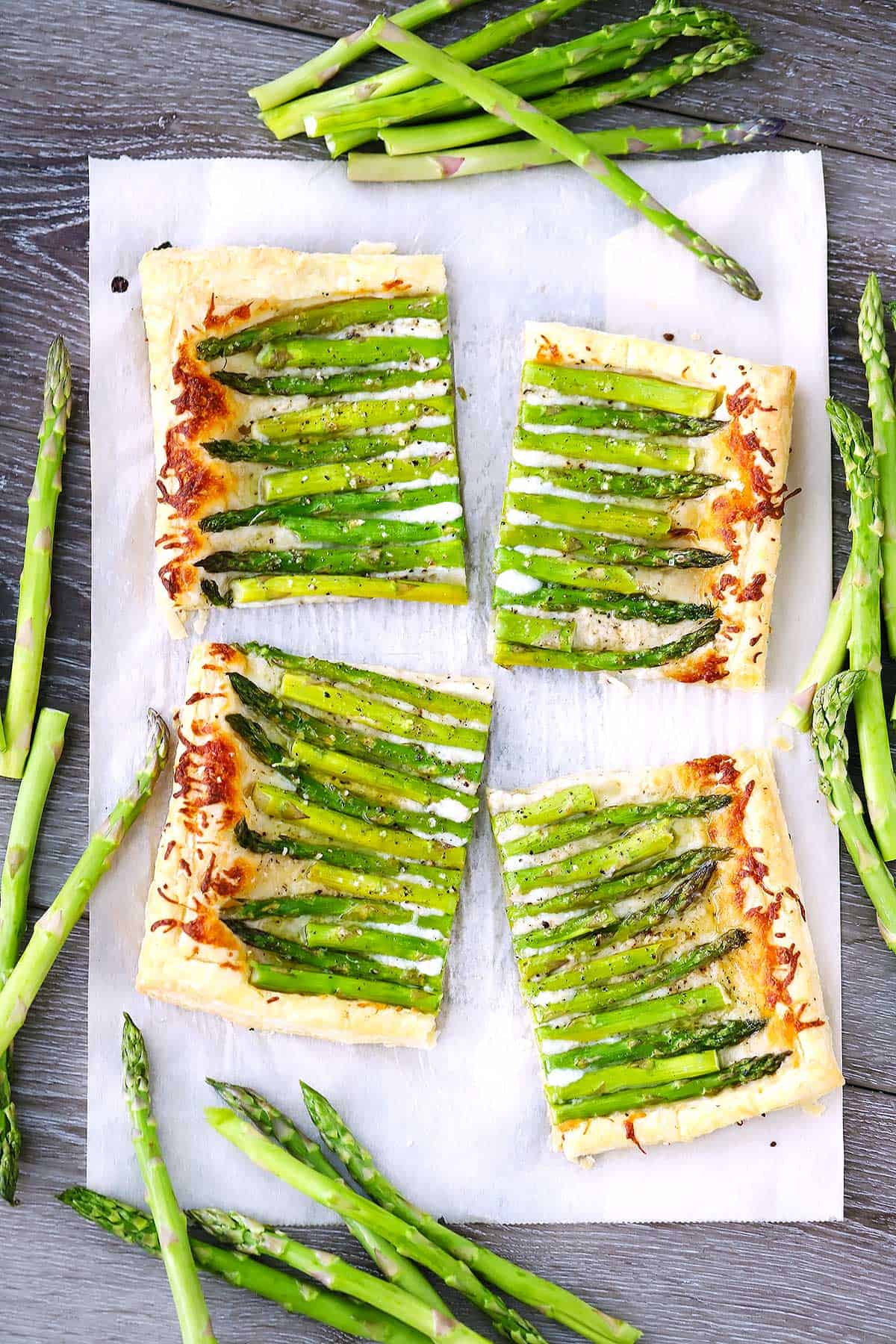 A puff pastry asparagus tart cut into fourths.
