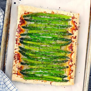An asparagus tart made with puff pastry on a baking sheet on parchment paper.