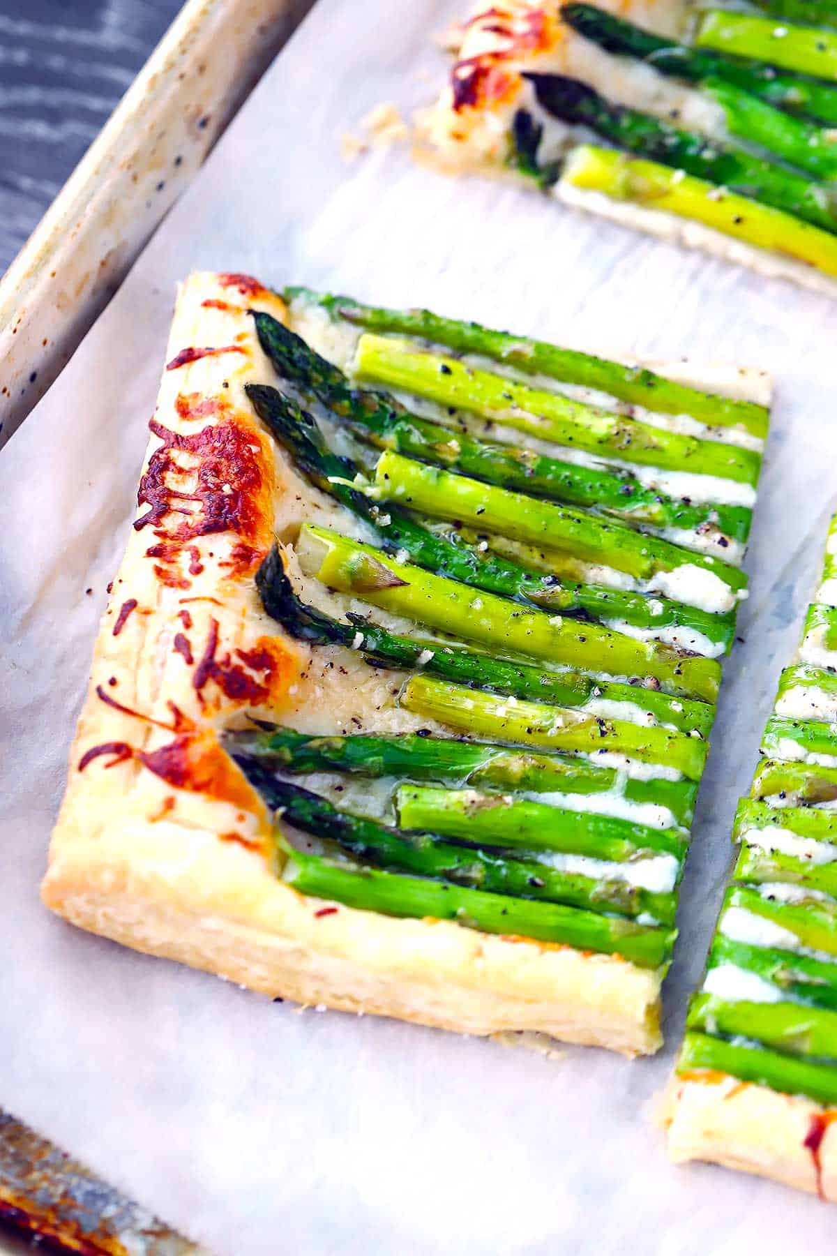 A close up version of a puff pastry asparagus tart cut into fourths.