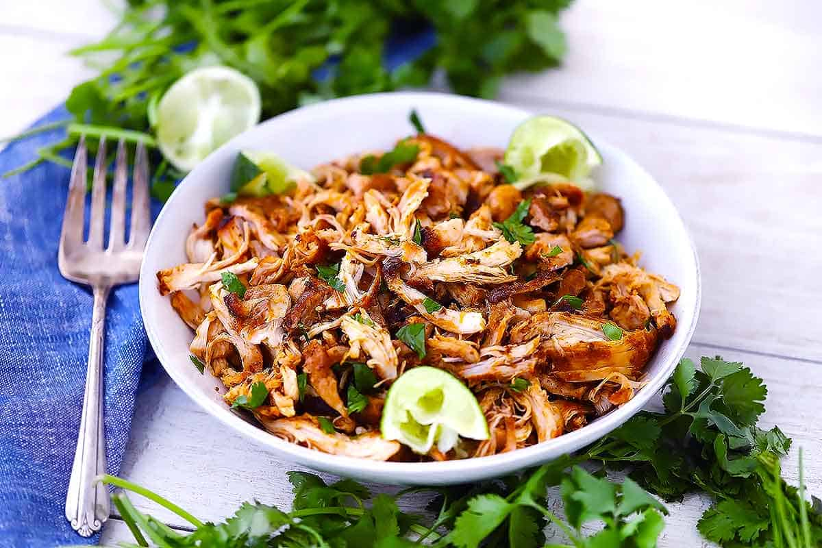 A white bowl with shredded Mexican chicken with cilantro and limes around it.