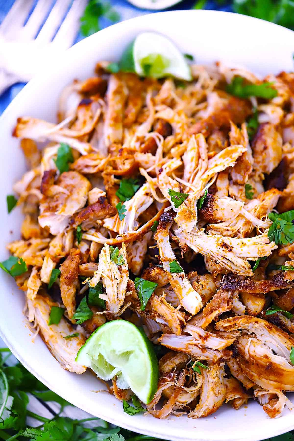 Close up overhead photo showing the texture of Mexican shredded chicken garnished with lime wedges and fresh cilantro.