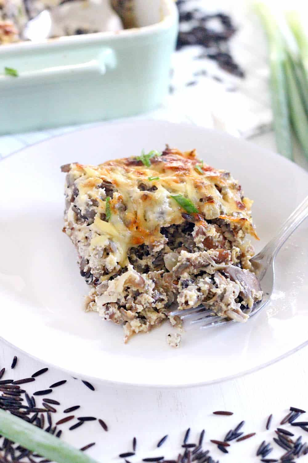 White plate with a square of casserole in the center, with uncooked wild rice scattered around and ceramic casserole dish in background.