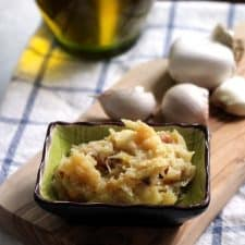 Square photo of small dish of roasted garlic paste in foreground on wooden cutting board, with garlic heads scattered in background.