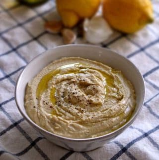 Roasted Garlic and Lemon Hummus | So easy to make at home, and SO much more affordable than pre-made. This recipe makes a ton, and has a delicious lemony tartness to it, which pairs extremely well with the cumin and roasted garlic flavors.