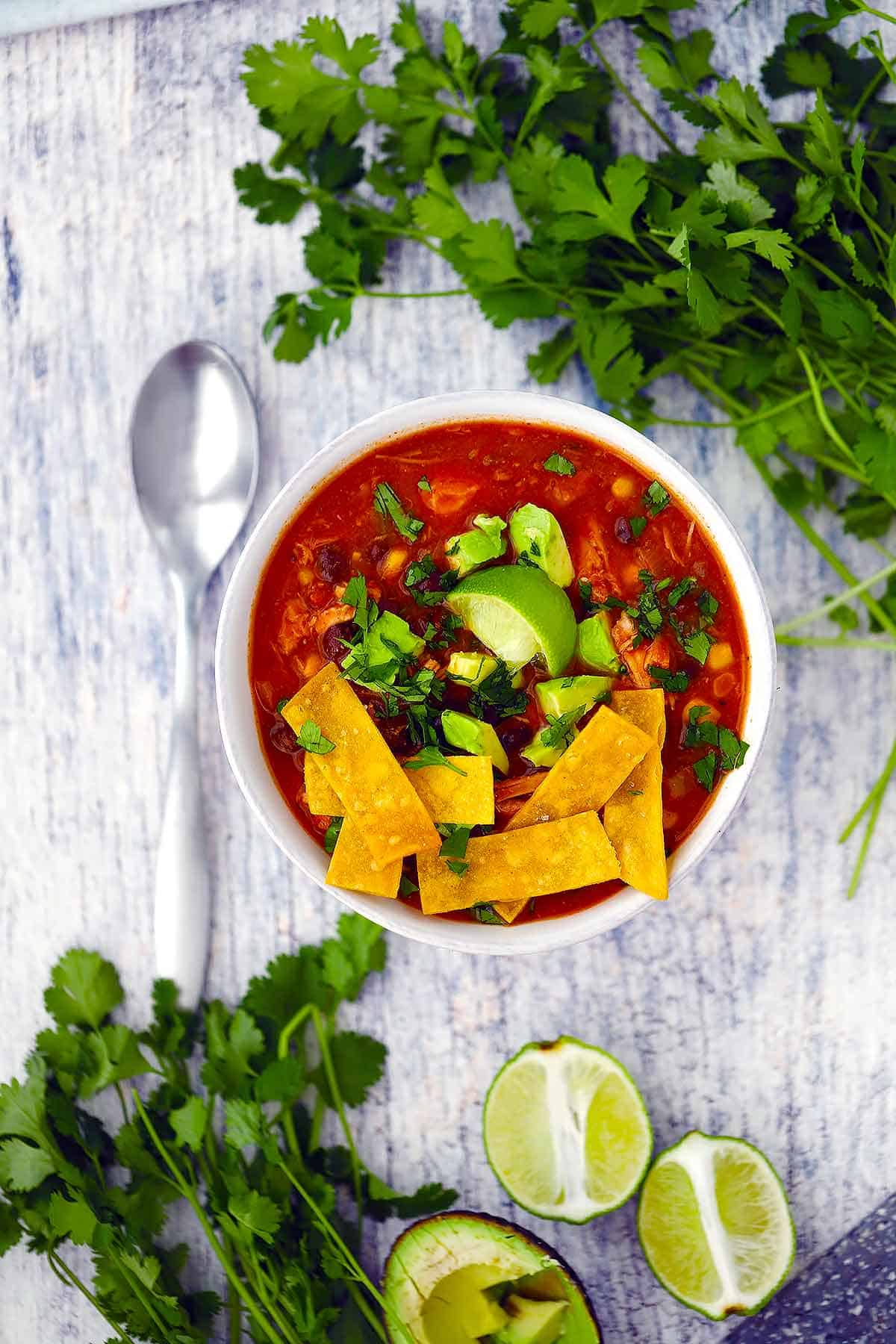 Overhead photo of a bowl of chicken tortilla soup surrounded by cilantro and limes.