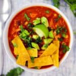 Square photo of smoked chicken tortilla soup topped with tortilla strips and avocado.