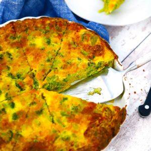 Square photo of crustless broccoli cheddar quiche sliced in a quiche dish.