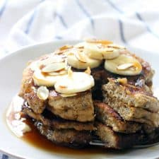 Stack of 3 pancakes on a white plate, sliced all the way through, topped with bananas, almonds, and syrup.