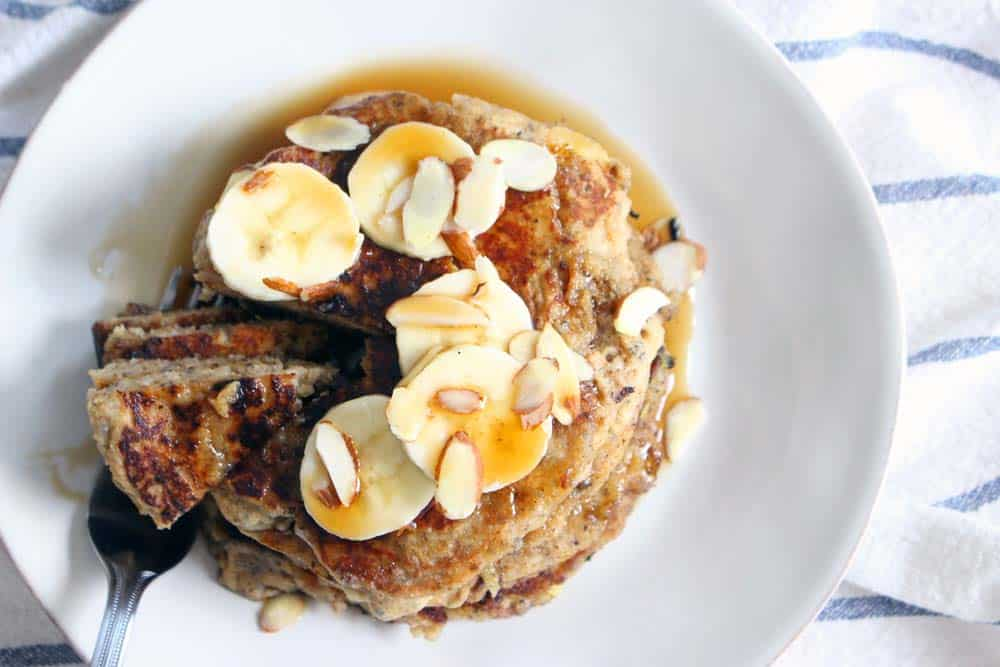 Bird's eye view of stack of pancakes on a white plate, topped with almonds, bananas, and syrup.