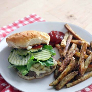 Cheeseburger with pickles, ketchup, and lettuce on a white plate with french fries and a dollop of ketchup, on a red and white checkered tablecloth.