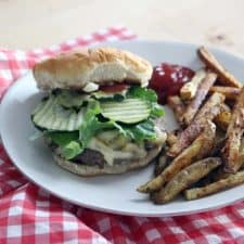 White plate holding cheeseburger with pickles, ketchup, and lettuce, as well as french fries and a dollop of ketchup, all on a red and white checkered cloth.
