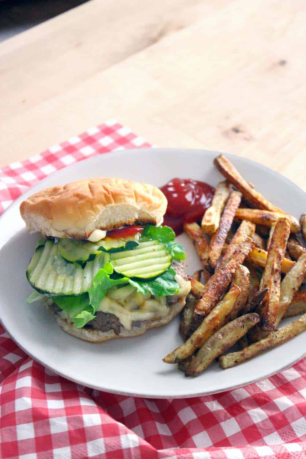 White plate holding cheeseburger with pickles, ketchup, and lettuce, as well as french fries and a dollop of ketchup, all on a red and white checkered cloth, on a wooden table.