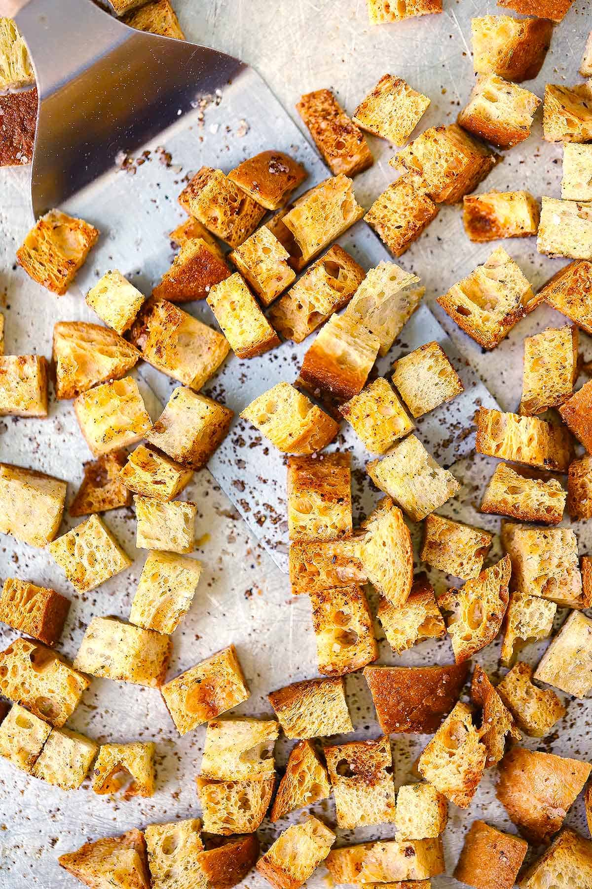 """Several croutons pictured on a white surface, with overlaid text that reads """"Homemade Whole Wheat Croutons."""""""