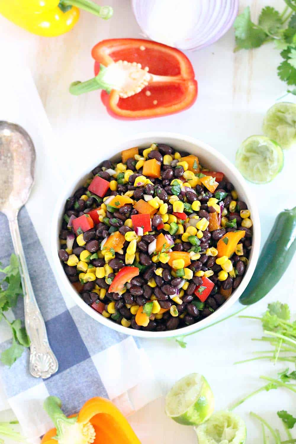 Bird's eye view of bowl of black bean and corn salad on a white surface with produce scattered around and a silver spoon next to the bowl.