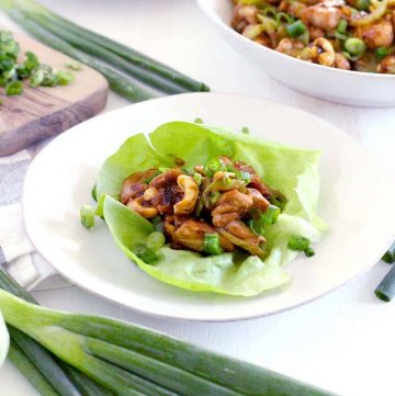 Open lettuce leaf on a white plate, with chicken and cashew mixture placed in the center.